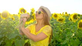 A menina da beleza com cabelo vermelho longo está no campo amarelo do girassol Mulher feliz ao ar livre teen teenager Cara Retrat filme