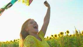 Menina da beleza com o cabelo vermelho longo que corre no campo amarelo do girassol com um papagaio Mulher feliz ao ar livre teen video estoque