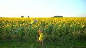 Menina da beleza com o cabelo vermelho longo que corre no campo amarelo do girassol com um papagaio Mulher feliz ao ar livre teen filme