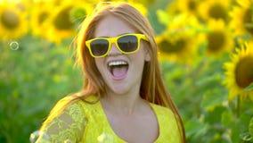 Menina da beleza com suportes vermelhos longos do cabelo em bolhas de sopro do ANG do campo amarelo do girassol Mulher feliz ao a vídeos de arquivo