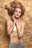 Menina da beleza da forma que encontra-se no brilho dourado fotos de stock