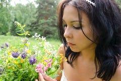 A menina da beleza em uma colheita do prado floresce, humor da mola foto de stock royalty free