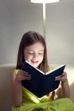 A menina da beleza leu o livro no sofá Imagem de Stock Royalty Free