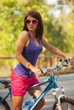 Menina da beleza na bicicleta no dia de verão. Fora Fotografia de Stock Royalty Free