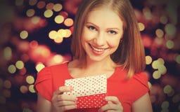 Menina da beleza no vestido vermelho com a caixa de presente ao dia do Natal ou de Valentim Foto de Stock