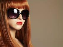 Menina da beleza nos óculos de sol Cabelo vermelho saudável Jovem mulher bonita com bordos vermelhos Imagem de Stock