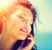 Menina da beleza que aplica Sun Tan Cream Imagem de Stock