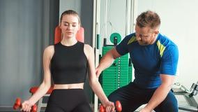 A menina da beleza que faz o peso exercita com auxílio de seu instrutor pessoal no gym filme