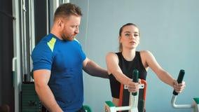 A menina da beleza que faz o peso exercita com auxílio de seu instrutor pessoal no gym video estoque