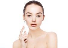 Menina da beleza que guarda o rolo da cara da massagem da drenagem foto de stock royalty free