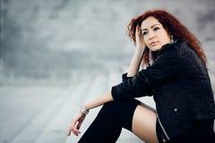 A menina da beleza senta no passos concretos Imagens de Stock