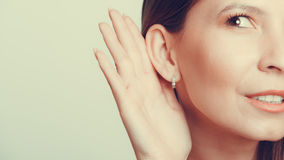 Menina da bisbolhetice que bisbilhota com mão à orelha Imagens de Stock