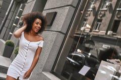 Menina da cidade com um grande estilo Mulher afro-americana bonita no vestido do hite que joga com seu cabelo ao andar abaixo do fotografia de stock