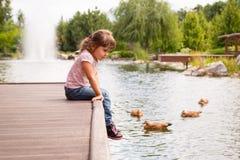 A menina da criança é melancolia que senta-se no cais Foto de Stock Royalty Free