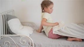 A menina da criança acorda do sono Uma menina agradável da criança aprecia a manhã ensolarada Bom dia em casa