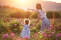 A menina da criança bonita com a mãe nova está vestindo a roupa ocasional que anda no jardim de rosas sobre luzes do por do sol Imagem de Stock