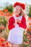 Menina da criança bonita no campo da mola com papoilas Imagens de Stock