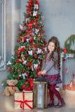 Menina da criança com a caixa de presente perto da árvore e da chaminé de Natal em casa fotografia de stock