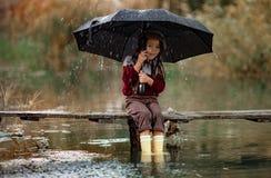 A menina da criança com guarda-chuva senta-se na ponte de madeira e nos sorrisos no rai imagem de stock