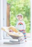 Menina da criança com o irmão recém-nascido que relaxa no balanço Imagens de Stock Royalty Free