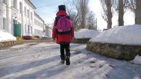 A menina da criança com saco vai à escola primária Criança da escola primária O aluno vai estudo com trouxa video estoque
