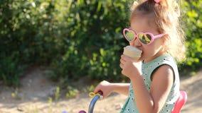 A menina da criança come o gelado nos óculos de sol em um dia de verão ensolarado filme