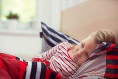 Menina da criança consideravelmente pequena que coloca no chá da cama e da bebida fotografia de stock
