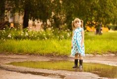 A menina da criança corre através de uma poça ver?o fotos de stock royalty free