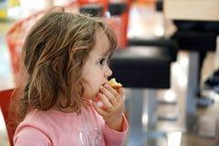 A menina da criança de 4 anos come um bolo em um shopping fotografia de stock