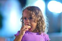 A menina da criança de 3 anos come um gelado fotos de stock