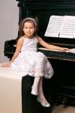 Menina em um vestido preto que senta-se perto do piano Imagem de Stock