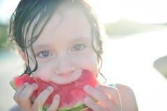 Menina da criança de 6 anos que come a melancia no verão Imagens de Stock