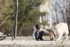 Menina da criança de 10 anos que dá o alimento a seu cão fora Imagens de Stock