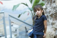 Menina da criança de 10 anos que descansa em uma rocha que olha a câmera Fotos de Stock