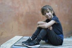 Menina da criança de 10 anos que senta-se em um banco de madeira Fotografia de Stock Royalty Free