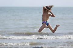 Menina da criança de 10 anos que tem o divertimento em uma praia Foto de Stock