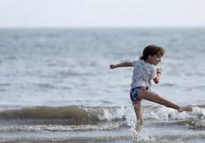 Menina da criança de 10 anos que tem o divertimento em uma praia Fotografia de Stock