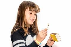 Menina da criança de oito anos que joga com os fósforos isolados no branco Imagem de Stock