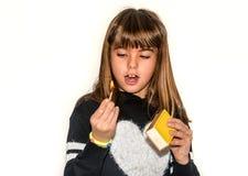 Menina da criança de oito anos que joga com os fósforos isolados no branco Imagem de Stock Royalty Free