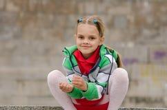 A menina da criança de seis anos agachou-se no fundo de uma parede do granito Fotografia de Stock Royalty Free