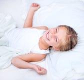 Menina da criança de seis anos em uma cama branca Fotos de Stock Royalty Free