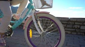A menina da criança de seis anos monta uma bicicleta à escola na manhã ao longo da frente marítima filme