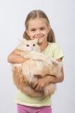 Menina da criança de seis anos que guarda o gato doméstico adulto Imagem de Stock Royalty Free