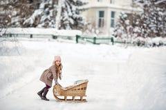 Menina da criança de seis anos que joga com os trenós do vintage no inverno Fotografia de Stock