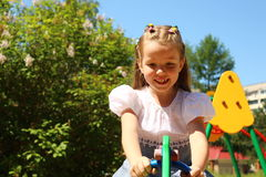 Menina da criança de sete anos em um balanço no campo de jogos Fotografia de Stock Royalty Free
