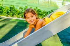 Menina da criança de sete anos que joga no campo de jogos Foto de Stock