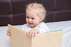 Menina da criança de três anos que lê um livro imagens de stock