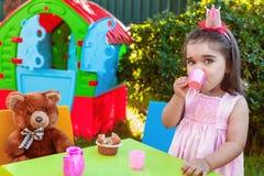 Menina da criança do bebê que joga no tea party exterior que bebe do copo com melhor amigo Teddy Bear Fotos de Stock