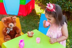 Menina da criança do bebê que joga no tea party exterior que bebe do copo com melhor amigo Teddy Bear Imagem de Stock