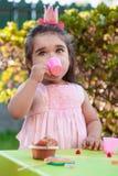 Menina da criança do bebê que joga no tea party exterior que bebe do copo com pirulito, queque e gummies na tabela Imagens de Stock